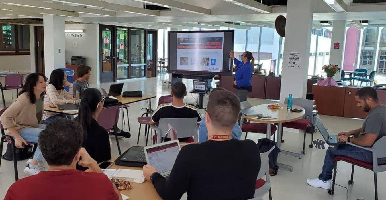 Imagen Estudiantes sentados en sus mesas antendiendo a la conferenciante del taller