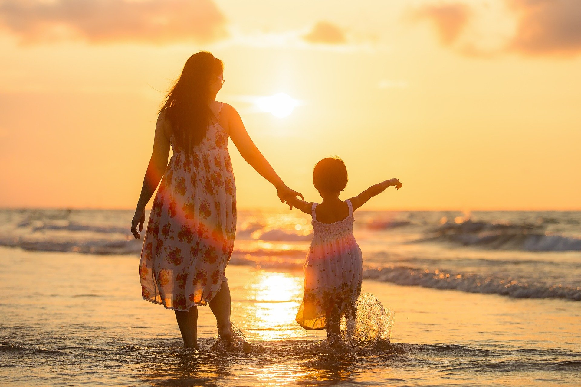 imagen madre e hija caminando hacia la playa