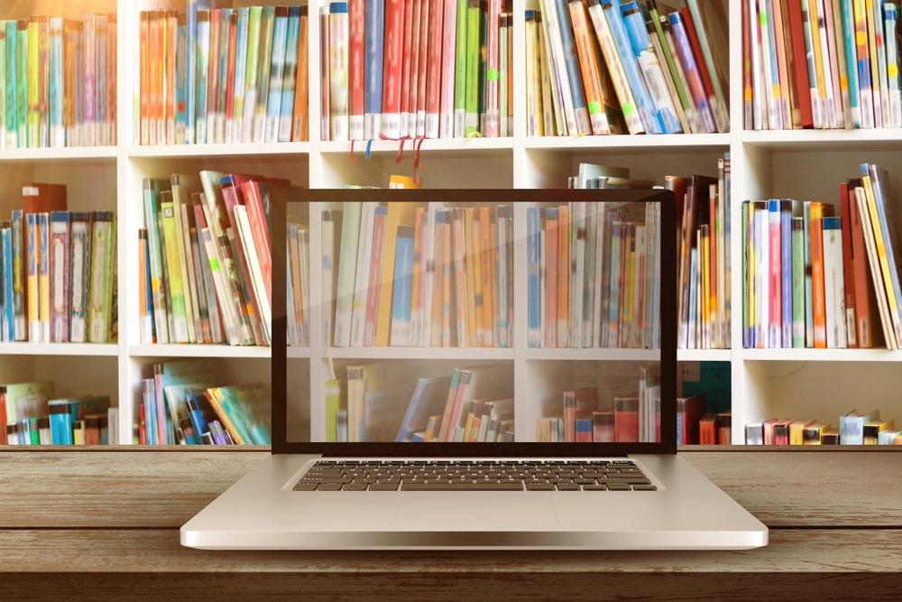 Presiona esta imagen de una computadora portatil mirando a unos estantes de libros para ver el video