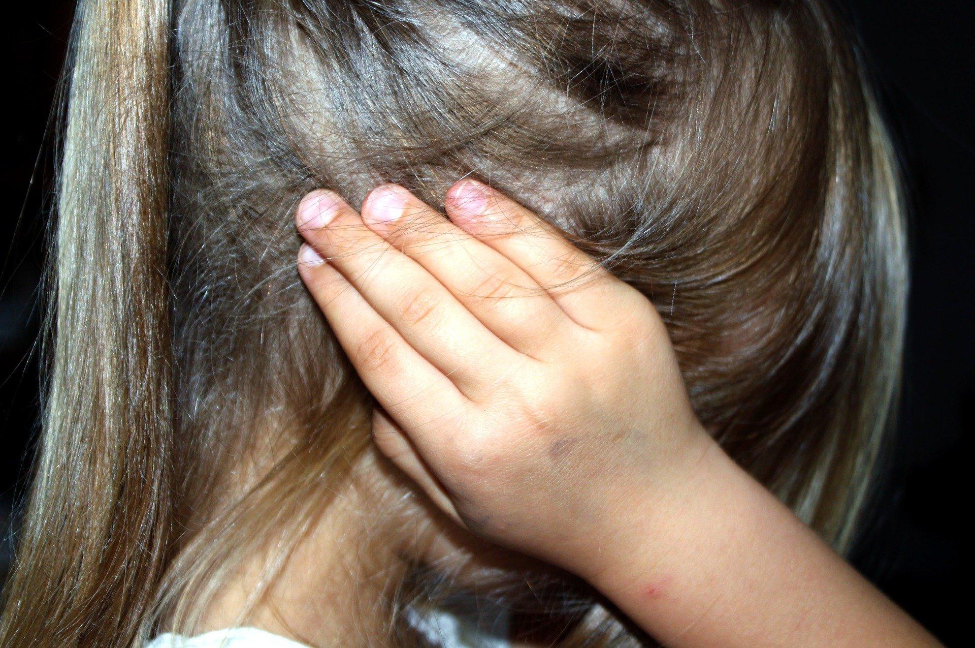 imagen niña temerosa de perfil tapandose los oidos con las manos