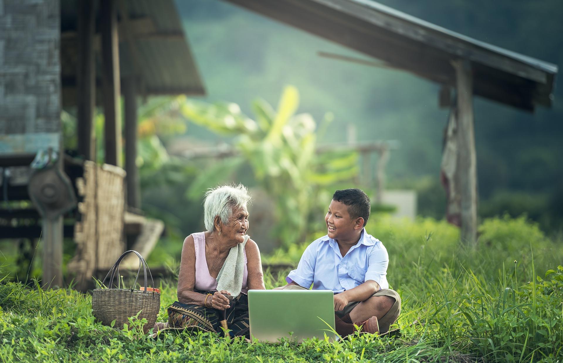 anciana y niño a la disstancia mirandose y sonriendo con una computadora entre ellos